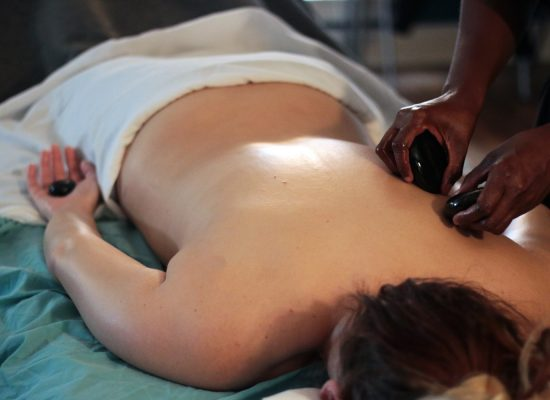 Massage student performing stone massage techniques